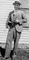 John Dillinger posing with tommy gun and pistol